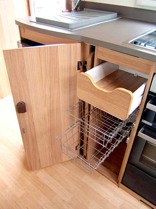 The cupboard below the woktop with storage baskets and cutlery drawer.