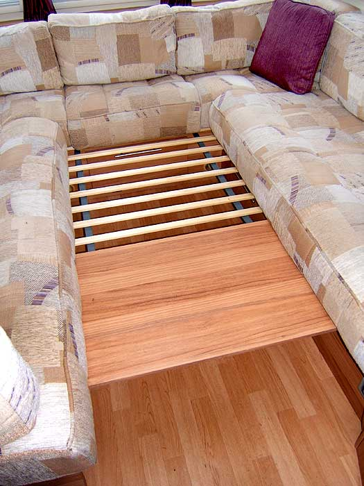 This 'array' of wooden slats pulls out from under the drawer cabinet between the seats and aids the process of converting the front lounge to and from a sleeping area.