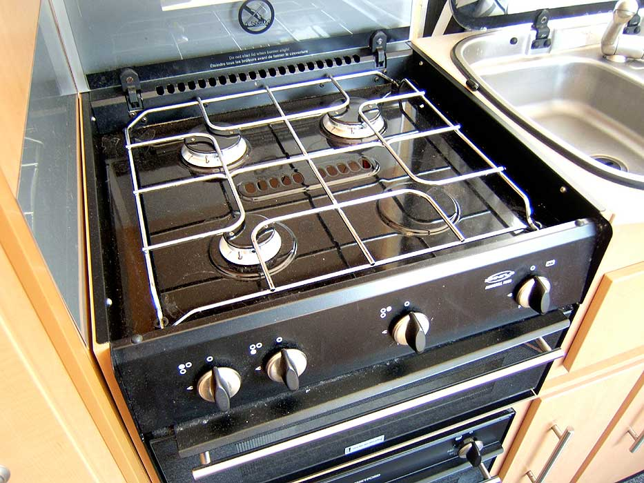 A close-up of the hob unit - with 3 gas burners and an electric hotplate.